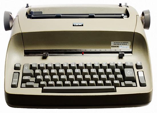 Vid sidan av skrivbordet, på ett litet rangligt bord med hjul, var IBMS elektriska skrivmaskiner vanliga på kontoren.