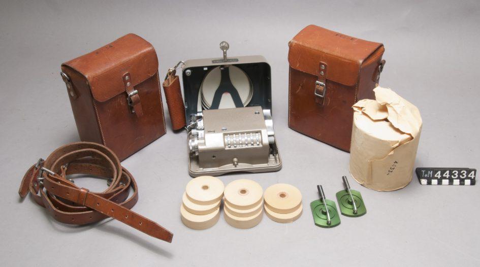 Kryptograf med pappersrullar och läderväska.